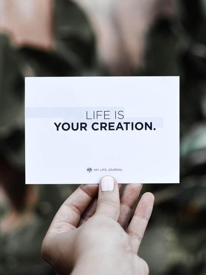 Image of a hand holding a card Written Life is your creation